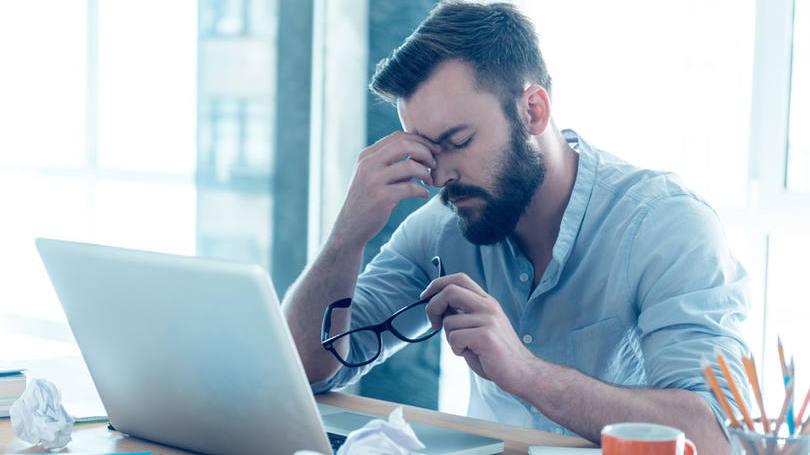 Homem com dor de cabeça: uma pessoa próxima da fadiga começa a apresentar mudanças de comportamento no trabalho